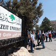 People stand near Birzeit University sign