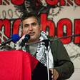 A man wearing a Palestinian scarf speaks at a podium
