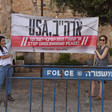 "Two women hold sign reading ""USA stop undermining peace"" in English and Hebrew"