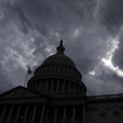 Dome of US Capitol against stormy sky