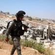 Soldier walks beside demolished building