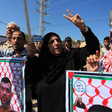 Palestinians hold banners, make peace sign with their hands