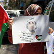 Woman holds Palestine flag and poster showing portrait of young man