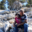 Man sits on rubble of a demolished home with young girl sitting on his leg