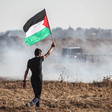 Man walks in front of tear gas cloud while holding Palestine flag