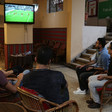 Five men watch football match on television