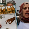 A woman holds a placard that says boycott Israel