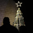 Silhouette of a man near a lit Christmas tree