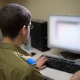 Man in military uniform sits in front of computer