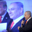 Benjamin Netanyahu speaks into a microphone in front of a picture of himself with US president Donald Trump