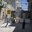 Two boys play with soccer ball in front of concrete blocks and metal barricade