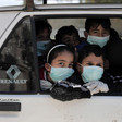 Children wearing face masks look out of vehicle window