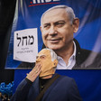 Man wearing a mask stands in front of Netanyahu banner