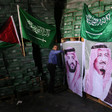 Man stands in front of stacked cartons with Palestinian and Saudi flags and portraits of Saudi royals displayed on them
