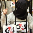 A protester wears a hood behind bars