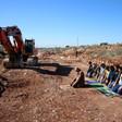 Men pray near construction equipment