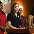Four women stand at podium