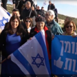 A group of people with Israeli flags and a banner in Hebrew