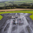A drone aircraft on a runway surrounded by fields and hills