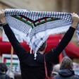 A man holds up a kuffiyeh scarf with a Palestinian flag inlay