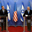 Two men stand at podiums with US and Israeli flags behind them