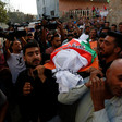 Crowd of men carry shrouded body on stretcher