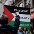 A man at a demo facing a Palestinian flag holds up his fist in solidarity