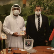 Four mean wearing protective masks hold plaques
