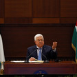 Mahmoud Abbas lifts hand in air while seated between two Palestinian flags