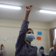 Girl raises fist while seated in a classroom