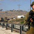 Armed Israeli soldier stands next to road with military vehicles behind him