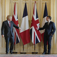 Boris Johnson and Emmanuel Macron stand in front of flags and point at each other