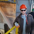 Man surrounded by machinery wears hard hat and sunglasses