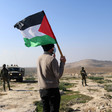 Man with back turned to camera holds Palestine flag while facing soldiers