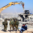 Heavily armed soldiers watch Hyundai bulldozer demolish a home while two men observe nearby