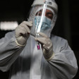 Man wearing protective gear places swab in test tube