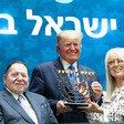 A man holding menorah candlestick flanked by a couple