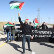 Man holds Palestine flag in air while standing in front of banner reading No to Apartheid No to Annexation