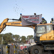 People on top of construction equipment hold banner