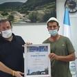 Two men wearing face masks hold framed certificate