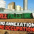 "Activists holding banners on a beach reading ""Free Palestine"" and ""No annexation, No occupation"""