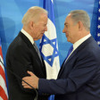 Joe Biden and Benjamin Netanyahu embrace in front of US and Israeli flags