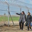 Two women stand beside large fence topped with barbed wire