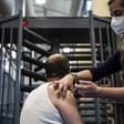 A standing, masked woman administers a vaccination to the shoulder of a man seated in front of metal turnstile