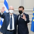 Reuven Rivlin and Emmanuel Macron, both wearing face masks, wave while standing in front of Israeli and EU flags