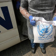 Man seen from chest down holds bag of UNRWA food aid in front of UN vehicle