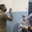 A uniformed soldier holds up a phone while a seated man receives a shot from a health care worker