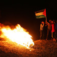 A small group of people stand next to a fire holding a Palestinian flag in the dark