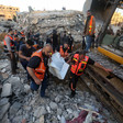 Men in emergency worker vests carry shrouded body away from destroyed building