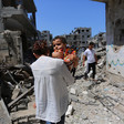 Girl holding baby is seen from back as she stands in bombed-out neighborhood